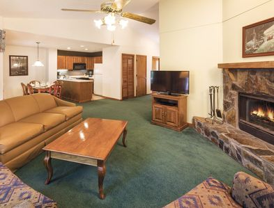 An open plan living room dining room and kitchen area with a fire in the fireplace.