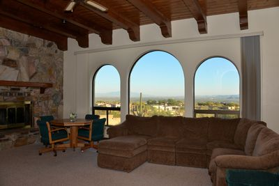 Main gathering room with flat screen TV, fireplace, couch and view of city.