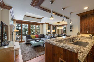 From the living area, access the unique private patio surrounded by pine trees.