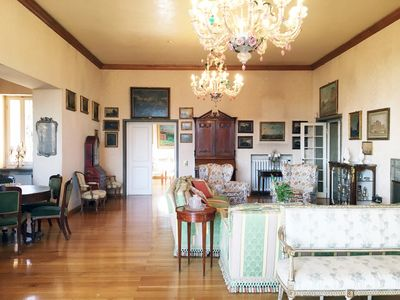 huge living room with fireplace, furnished with antiques and paintings