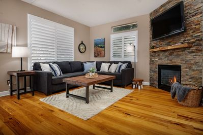 Spacious and comfortable living area with fireplace and flat screen TV.