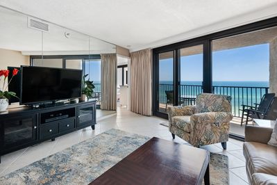 living room with beach background - large flat screen TV, shows entrance to master bedroom