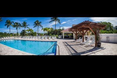 Tropical pool and sun deck area, complete with covered seating and chaise lounges for your use.