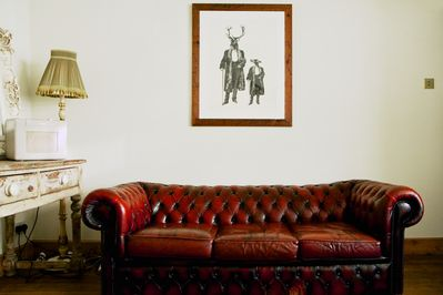 The lovely sitting room has three vintage chesterfield sofas which seat 6 people