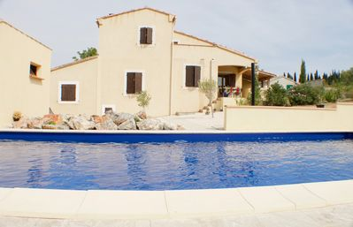 view of house and upper terrace over pool