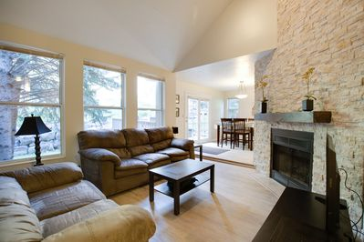 Living room with gorgeous gas fireplace with stone surround.