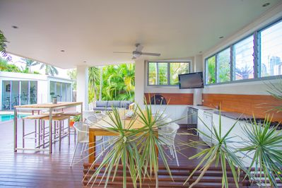 Breezy alfresco dining with ceiling fan, TV and outdoor kitchen