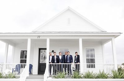 The groomsmen of a recent Adams Estate wedding relax on the front porch.