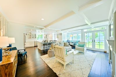 """This """"lots of windows"""" living room area of the great room is flanked by the kitchen with high top stools so everything flows with ease."""