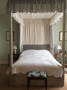 The master bedroom with a four poster bed and ensuite bathroom