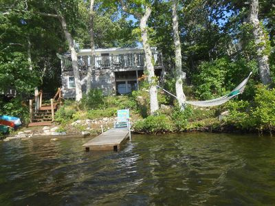 view of house, hammock and dock from lake