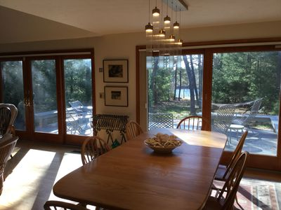 Dining room with sliders to the deck. You can see the water and secluded view