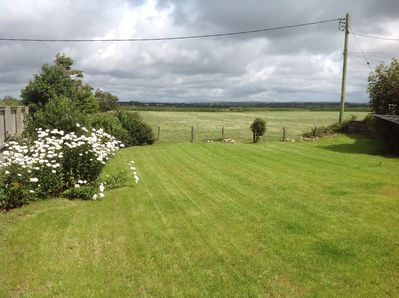 View of tranquil garden and countryside from lounge in holiday let