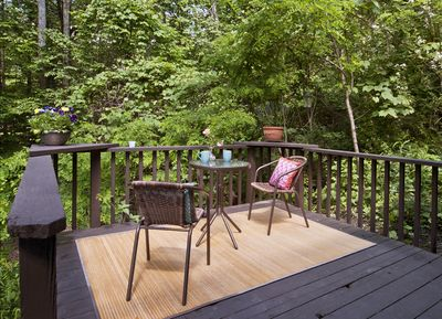 Relax on your private deck in the treetops overlooking a stream in the summer