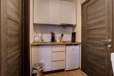 Private kitchen is equipped with dishes, teapot and fridge.