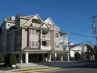 Outdoor shot with 2 parking spots and a deck facing the beach with an Oceanview