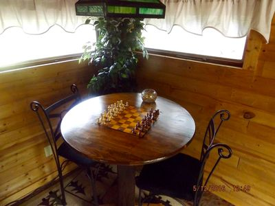 Table is multipurpose for a game of chess or checkers or a meal.