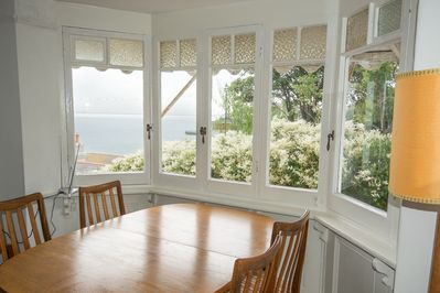 dining area looks out to sea with garden next door giving privacy
