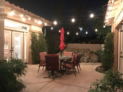 Front courtyard with patio lights, waterfall in background