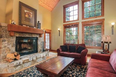 2 red couches next to brick fireplace