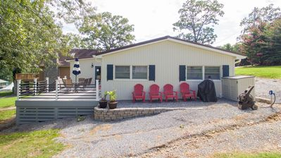 Side view of house. Large porch with patio furniture and grilling area. Lakeview