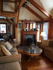Bright and comfortable sunroom looking at gas fireplace and towards library area