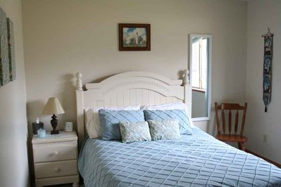 The master bedroom has a queen sized bed and a ceiling fan