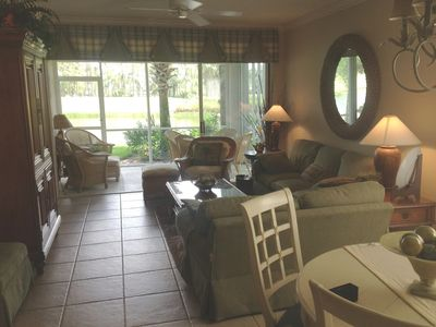 Spacious living room with view of golf course through lanai.