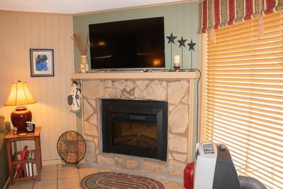 Electric fireplace with large-screen TV mounted above; HD channels and Google Chromecast