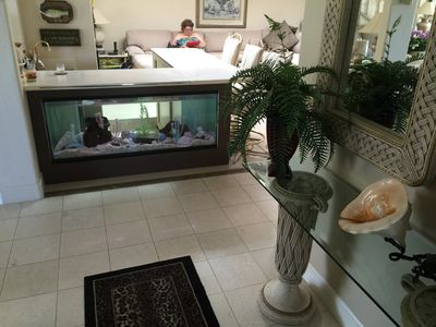 View from the entry showing built-in fish tank in the wet bar and the family rm.