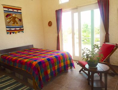 2nd floor bedroom-private bath, door to terrace, easy chair, small table, desk