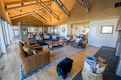 Living room and floating kitchen with 30ft ceilings and custom beam work