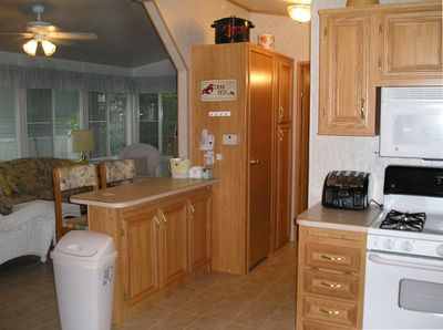 breakfast bar separates kitchen from sunroom; hall w/closets to large bedroom