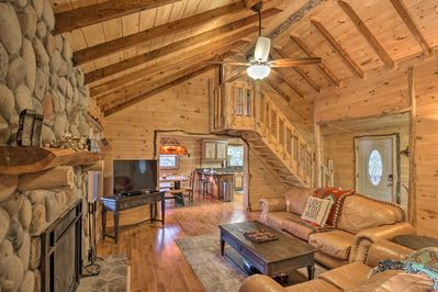 Forge a flame in the rustic floor-to-ceiling river rock fireplace.