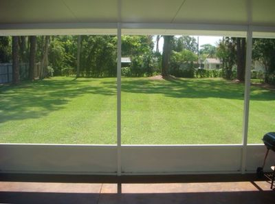 View of fully fenced back yard from 12 x 40 foot screened lanai
