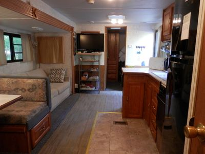 View of living room from kitchen showing TV, and bunk room