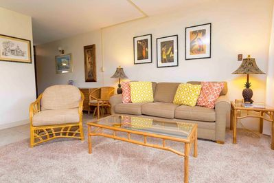 Tan couch with vibrant yellow and orange pillows and one rattan chair
