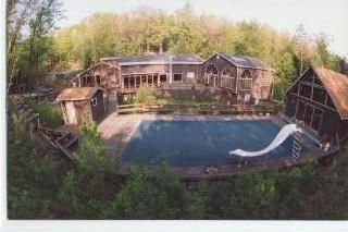 overview of house from bank behind pool. Slide and small pump house removed