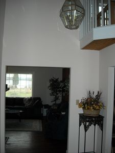 Entry foyer with loft overlook and view through living room to lawn and bay.