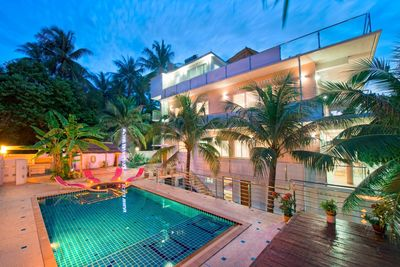 Villa is surrounded by beautiful palm trees and lush green vegetation.