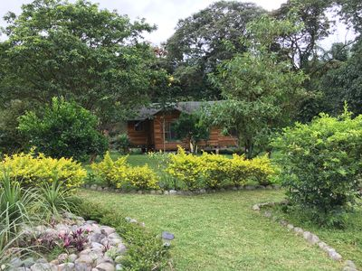 Front view of solar powered, off grid eco-cottage, surrounded by forest & garden