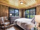 The queen bed in the main house master bedroom is surrounded by nature views and accessed through bedroom two.