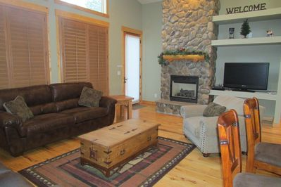 Floor to ceiling river rock fireplace, flat screen tv and entrance to patio.