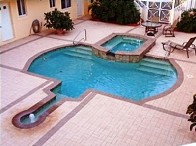 The pool with whirlpool and patio table, chairs and lounge chairs.