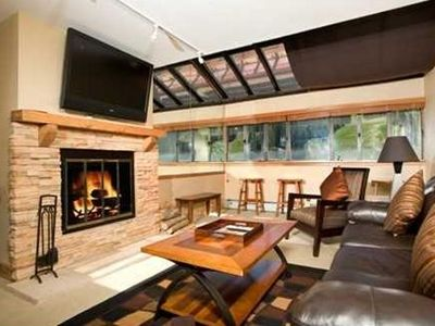 Spacious living room has beautiful mountain views & a wood-burning fireplace.