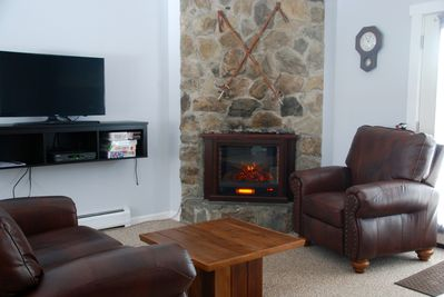 An electric fireplace heater sits in the corner of the sitting area.