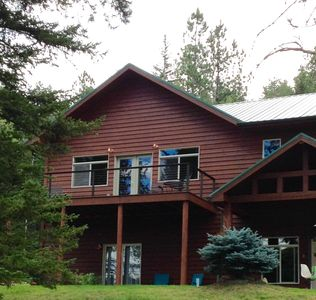 spacious upper deck with tables, chairs and recliner overlooks meadow and woods