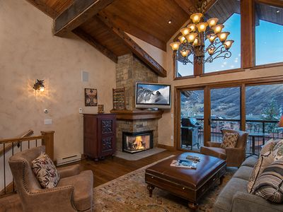 Cozy Living Room has soaring ceilings,2 story windows,fireplace,balcony
