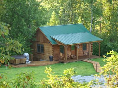 View of our Lazy Creek Cabin nestled in the woods with the creek behind it.