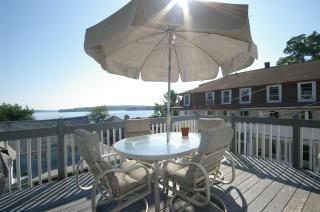 Deck with a gas grill and patio set.